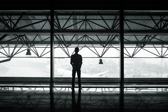 Man looks down in contemplation from a large balcony over an airfield