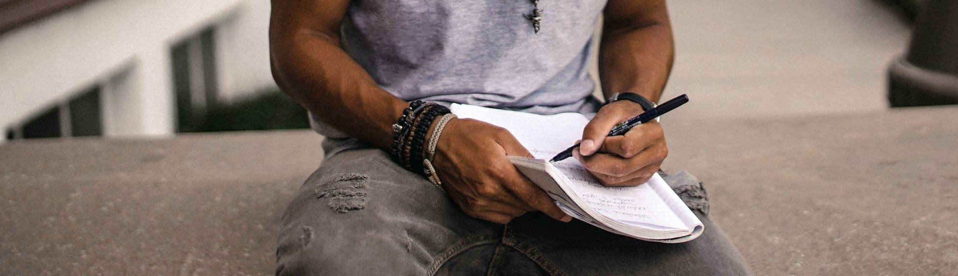 Man writing in notebook, cropped photo by Brad Neathery (@bradneathery) on Unsplash