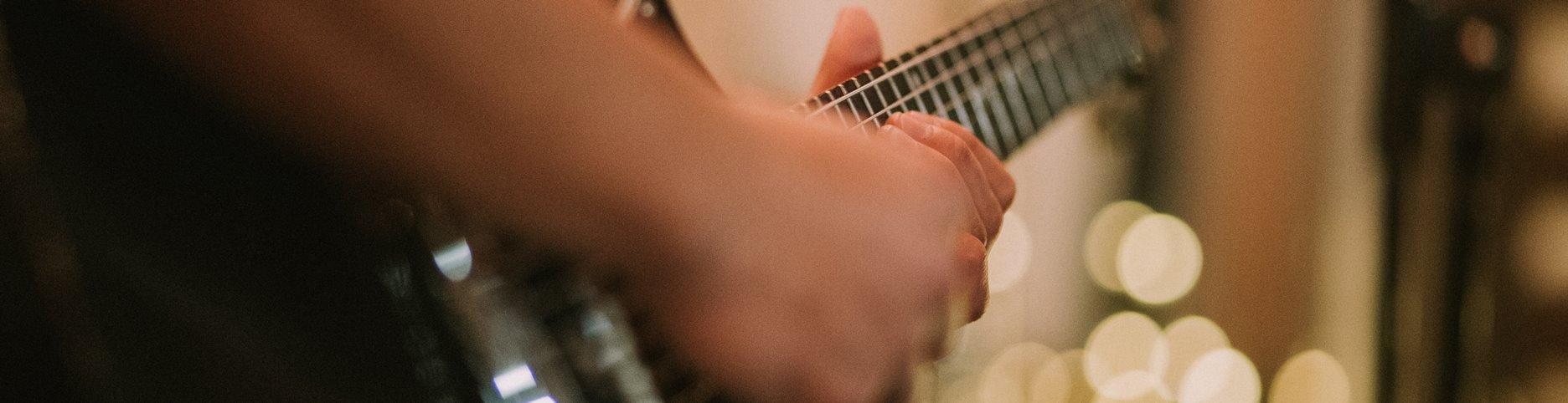 Hands strumming a guitar, cropped photo byAmy VelazquezonUnsplash