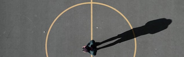 Man standing in painted circle on a court, cropped photo by Luís Eusébio on Unsplash